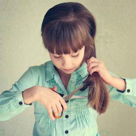 girl cut her hair. Toned image.