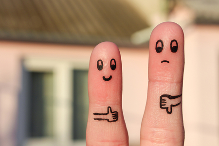 favorite: Finger art of couple. Woman showing thumbs up and man showing thumbs down. Concept of disagreement in family.