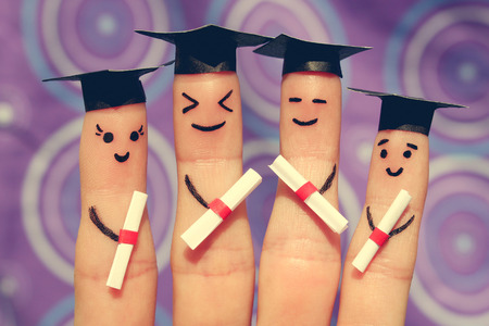 graduation party: Finger art of students. Graduates holding their diploma after graduation. Toned image