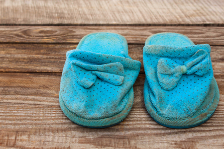 unsanitary: Old dirty homemade slippers on wooden background. Toned image.