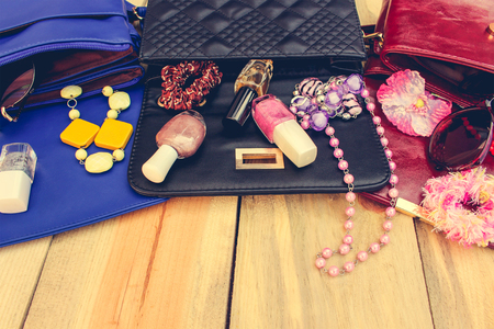 Cosmetics and women's accessories fell out of different handbag. Things from open lady handbag. Toned image.