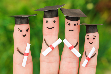 Finger art of students. Graduates holding their diploma after graduation. Toned image