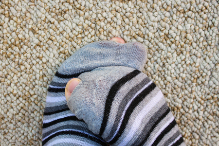 tatter: Closeup of striped socks full of holes Stock Photo