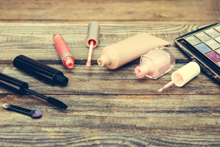 gloss: Cosmetics: mascara, concealer, nail polish, perfume, lip gloss and eye shadow on wooden background. Toned image.