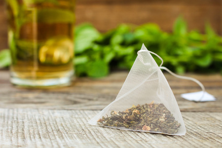 Tea bag on background of mint and and cup of tea