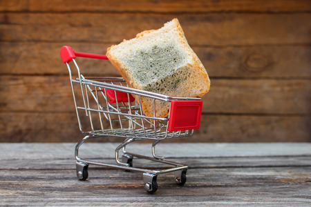 mildewed: Shopping cart with mold on bread on the old wood background. Mold on food. The concept of selling spoiled food. Toned image.