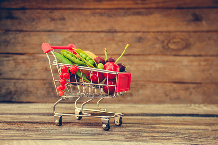 Shopping cart with fruits and berries on old wood background. Toned image.