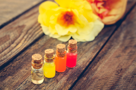 traquility: Bottles of essential oil and roses on old wooden background. Toned image