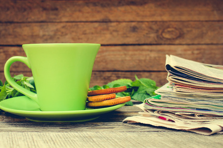 Cup of tea, mint, cookie, bunch of newspapers and magazines on wooden background. Toned image.
