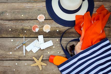 Summer vrouwen strand accessoires voor uw zee vakantie en pil op oude houten achtergrond. Concept van medicatie nodig reis Stockfoto