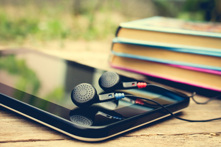 audio book: Headphones, tablet and stack of books. Toned image.