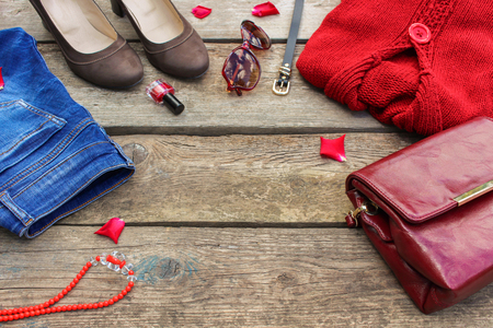 Womens autumn clothing and accessories: red sweater, jeans, handbag, beads, sunglasses, nail polish, shoes, belt on wooden background. Toned image.