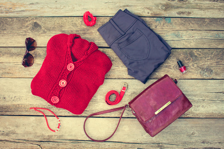 hair band: Womens autumn clothing and accessories: red sweater, pants, handbag, beads, sunglasses, nail polish, hair band, belt on wooden background. Toned image.
