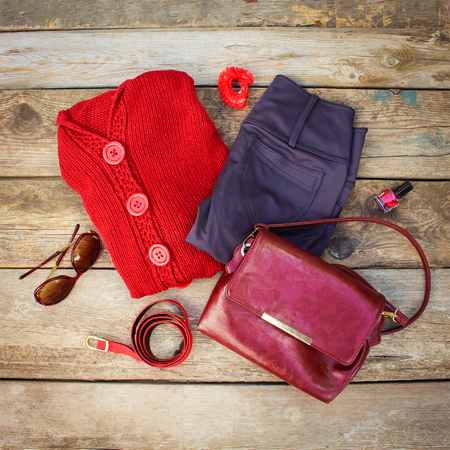 hair band: Womens autumn clothing and accessories: red sweater, pants, handbag, beads, sunglasses, nail polish, hair band, belt on wooden background. Top view.