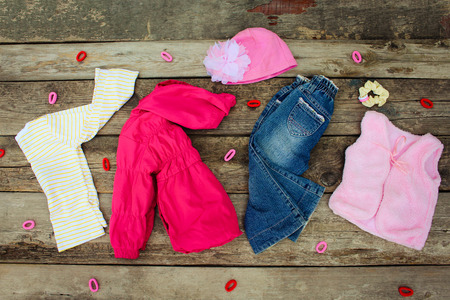 Childrens clothing and accessories: jeans, jacket, hat, hair clips and warm vest on old wooden background. Top view.