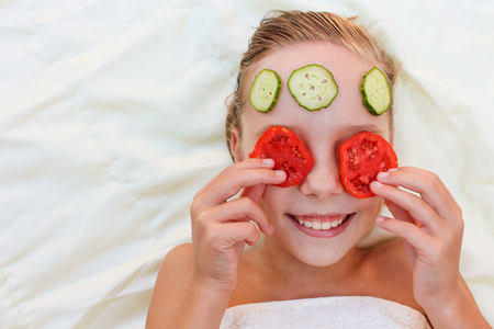 face mask: Close up of beautiful girl with facial mask of cucumber and tomatoes.