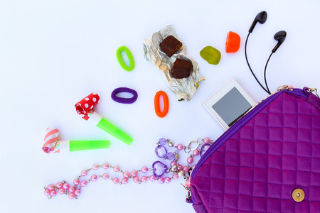 Childrens handbag and accessories: mobile phone, whistle, hair bands, candy, beads, headphones on white background. Top view.