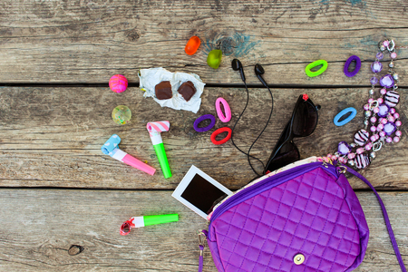 sweet stuff: Childrens handbag and accessories: mobile phone, whistle, hair bands, candy, beads, headphones, sunglasses, ball on old wooden background. Top view.