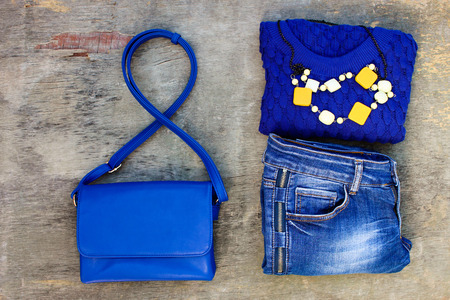 warm things: Womens autumn clothing and accessories: blue sweater, jeans, handbag, beads on wooden background. Top view.