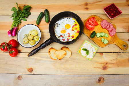 smoked: Different food: scrambled eggs in frying pan, boiled potatoes, curd, croutons, radishes, cucumbers, tomatoes, smoked sausage, mint, sorrel on wooden table.