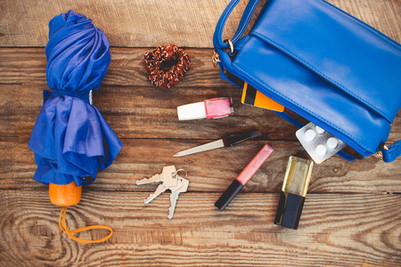 Blue purse, umbrella and women's accessories. Things from open lady handbag. Top view. Toned image.
