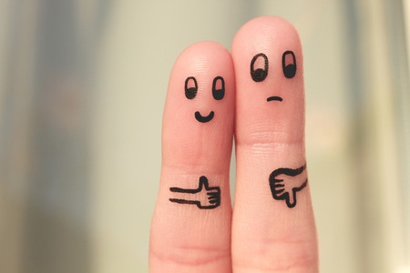 Finger art of couple. Woman showing thumbs up and man showing thumbs down. Concept of disagreement in family. Toned image.