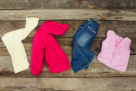 children clothing: Childrens clothing and accessories: jeans, jacket, hair clips and warm vest on old wooden background. Top view.