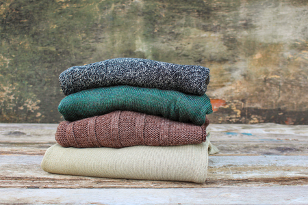 necessities: Pile of colorful warm clothes on wooden background.