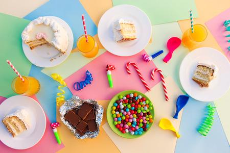 trozo de pastel: Torta, caramelo, chocolate, silbatos, serpentinas, globos, jugo en la mesa de vacaciones. Concepto de la fiesta de cumpleaños de los niños. Vista desde arriba.