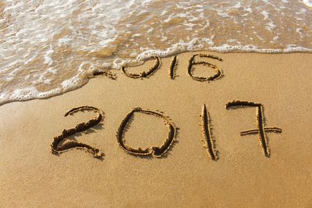 2016 and 2017 year written on sandy beach sea.
