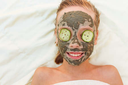 clays: Beautiful girl with facial clay and cucumber mask.