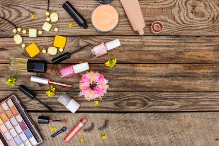 set up: Cosmetics: mascara, beads, elastic hair band, false eyelashes, concealer, nail polish, perfume, eyeliner, powder, lip gloss, eye shadow and yellow flowers on wooden background. Top view