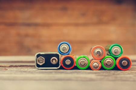 Many batteries on old wood background. Toned image