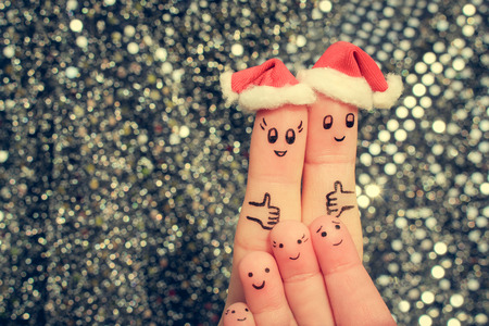 Finger art of large family celebrates Christmas. Concept of group of people laughing in new year hats. Happy couple showing thumbs up. Toned image