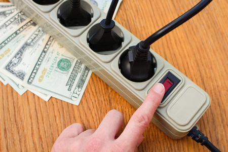 Womans hand turns off outlet. Concept of energy savings. Stock Photo