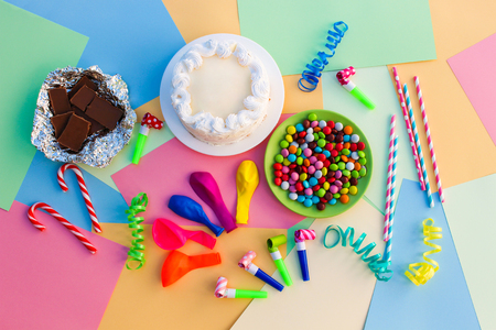 childrens birthday party: Cake, candy, chocolate, whistles, streamers, balloons on holiday table. Concept of childrens birthday party. View top.