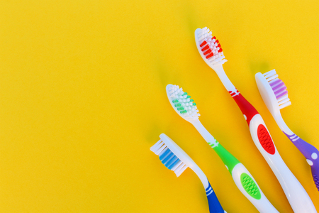 Toothbrushes on yellow background. Top view.