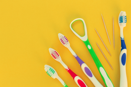 tongue cleaner: Toothbrushes, toothpick, tongue scraper on yellow background. Top view. Toned image.