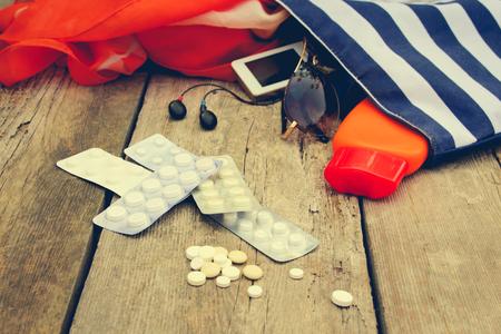 Summer vrouwen strand accessoires voor uw zee vakantie en pil op oude houten achtergrond. Concept van medicatie nodig is in de reis. Gestemd beeld.