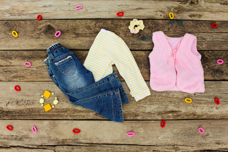 warm clothing: Childrens clothing and accessories: jeans, hair clips, blouse, warm vest on old wooden background. Top view.