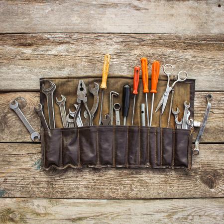 Oude hulpmiddelen in een zak op houten achtergrond. Bovenaanzicht.