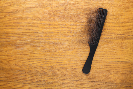 Fallen hair on comb on table. Top view.
