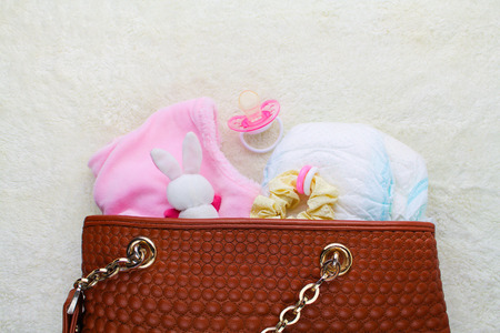 Mother's handbag with items to care for child on white background. Top view. Foto de archivo