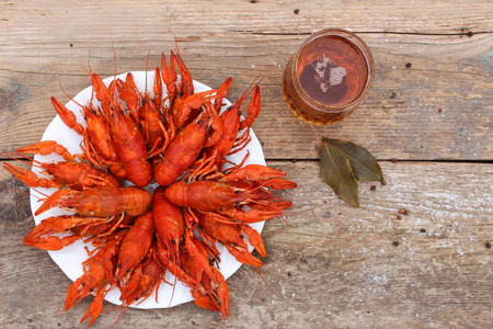 Crawfish and beer on the old wooden background. Top view. Stock Photo