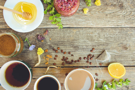Tea, coffee, cocoa in cups, chicory, lemon, mint, jam made of rose petals, dried lime, honey on the old wooden background. Toned image. Top view.