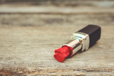오래 된 목조 배경에 깨진 된 빨간 립스틱입니다. 톤된 이미지입니다. 스톡 콘텐츠