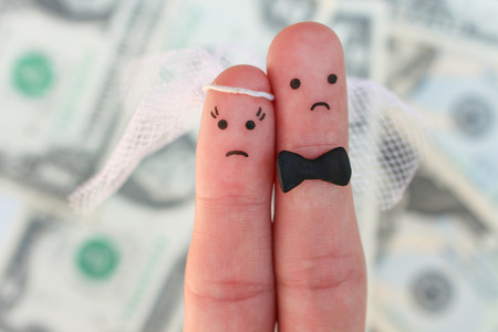 Fingers art of couple on background of money. Concept of wedding, woman and man needs to get married, but they do not want. Arranged marriage.