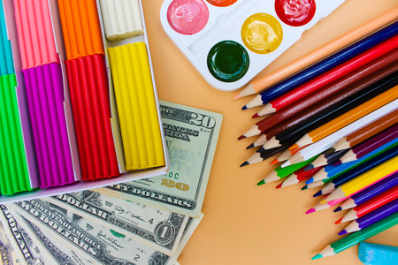 School supplies and dollars. Concept is to buy stationery objects Stock Photo