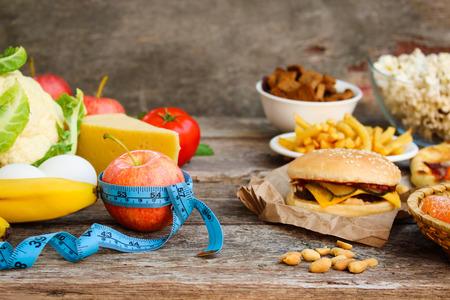 ファーストフードと古い木製の背景に健康食品。食べることの概念。