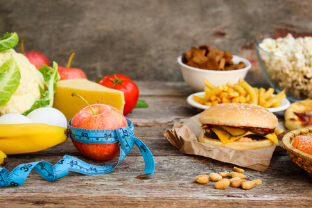 Fastfood and healthy food on old wooden background. Concept of eating.